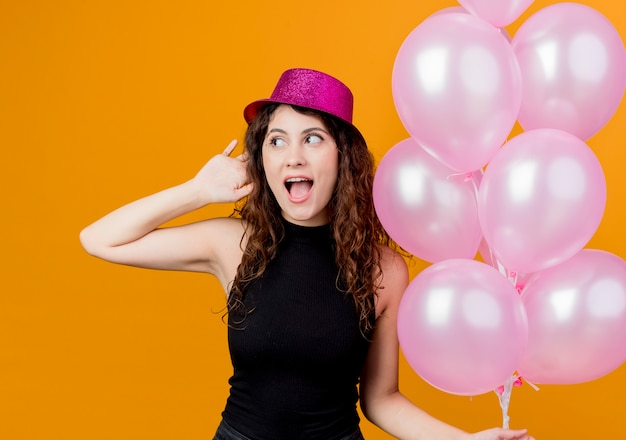 Jovem mulher bonita com cabelo encaracolado com um chapéu de férias segurando um monte de balões de ar feliz e animada sorrindo alegremente conceito de festa de aniversário em pé sobre a parede laranja