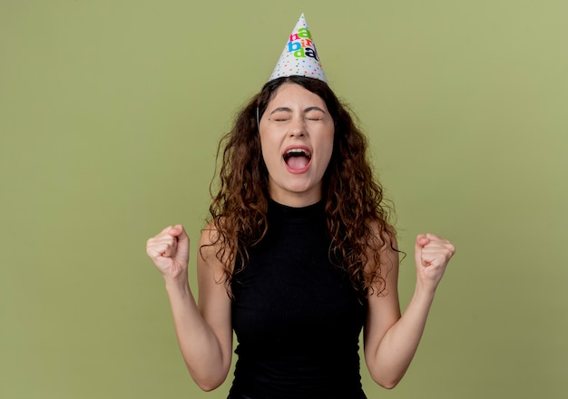 Jovem mulher bonita com cabelo encaracolado com um chapéu de natal cerrando os punhos, feliz e animada em pé sobre a parede de luz