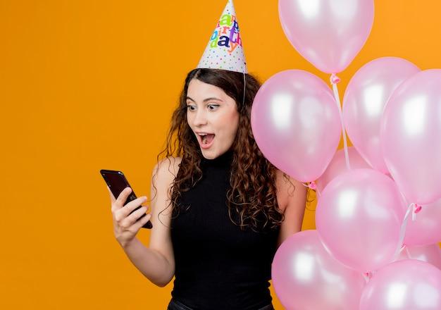 Jovem mulher bonita com cabelo encaracolado em um boné de férias segurando balões de ar, olhando para a tela de seu smartphone conceito de festa de aniversário feliz e animado em pé sobre a parede laranja