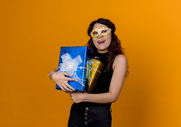 Jovem mulher bonita com cabelo encaracolado numa máscara de festa segurando presentes, feliz e animada em pé sobre uma parede laranja