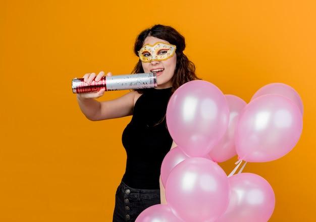 Jovem mulher bonita com cabelo encaracolado segurando um monte de balões de ar na máscara de festa conceito de festa de aniversário feliz e alegre sobre laranja