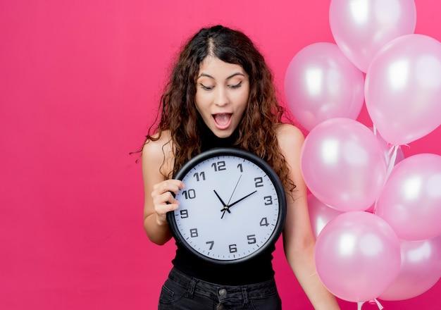 Jovem mulher bonita com cabelo encaracolado segurando um monte de balões de ar, relógio de parede olhando para ele surpresa e maravilhada em pé sobre a parede rosa