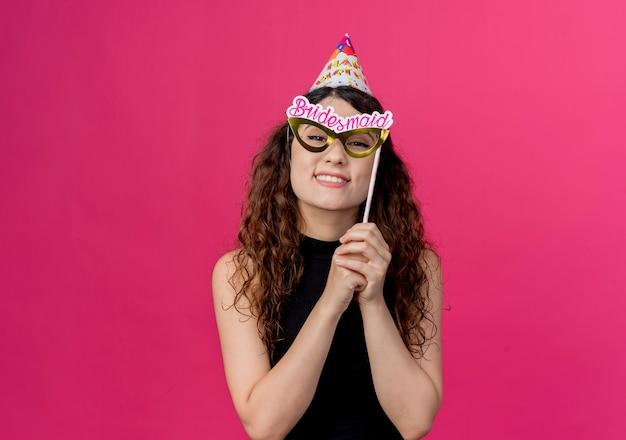 Jovem mulher bonita com cabelo encaracolado segurando um palito de festa feliz e alegre sorrindo em pé sobre a parede rosa