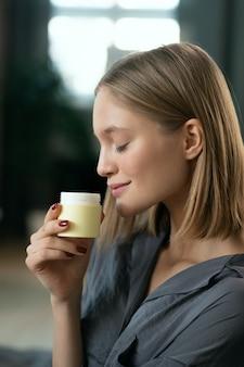 Jovem mulher bonita com cabelo loiro apreciando o cheiro de um produto cosmético natural feito à mão em um pequeno pote de plástico antes de aplicá-lo na pele
