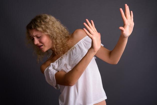 Jovem mulher bonita com cabelo loiro encaracolado contra grisalho