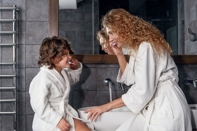 Jovem mulher bonita com cabelo loiro ensina seu filho encaracolado a escovar os dentes usando uma escova de dentes e creme dental.