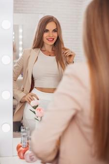 Jovem mulher bonita com cabelo loiro longa e saudável se olhando no espelho em um salão de cabeleireiro