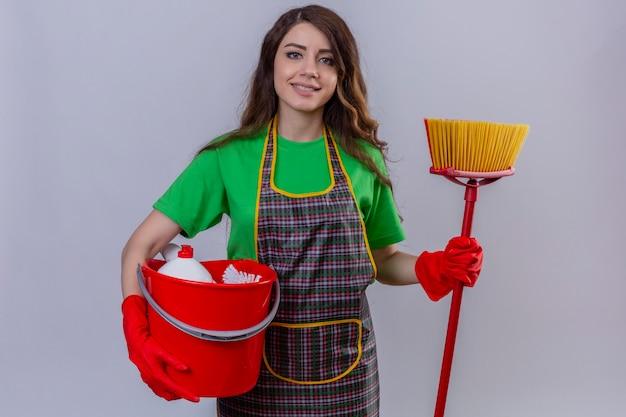 Jovem mulher bonita com cabelo longo ondulado em avental e luvas segurando um balde com ferramentas de limpeza e esfregão sorrindo alegre em pé