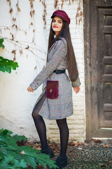 Jovem mulher bonita com cabelo muito comprido, vestindo casaco de inverno e boné no fundo de folhas de outono