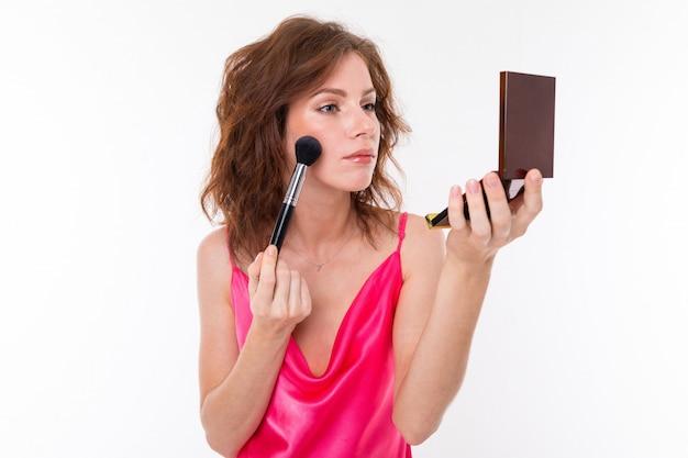 Jovem mulher bonita com cabelos castanhos ondulados, pele limpa, dentes planos, sorriso lindo, em jersey rosa, com pincel de maquiagem, pó e espelho faz maquiagem