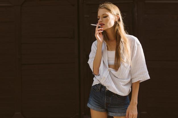 Jovem mulher bonita com camisa branca e shorts jeans, fumando um cigarro pensativamente