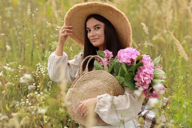 Jovem mulher bonita com chapéu de palha está segurando um buquê de flores cor de rosa. dia internacional da mulher.