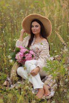 Jovem mulher bonita com chapéu de palha está segurando um buquê de hortênsia flores cor de rosa em um canudo. dia da mulher.