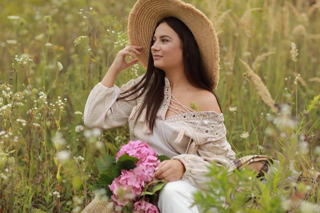Jovem mulher bonita com chapéu de palha está segurando um buquê de hortênsias de flores cor de rosa em um saco de palha ao ar livre sentado na grama num dia de verão.