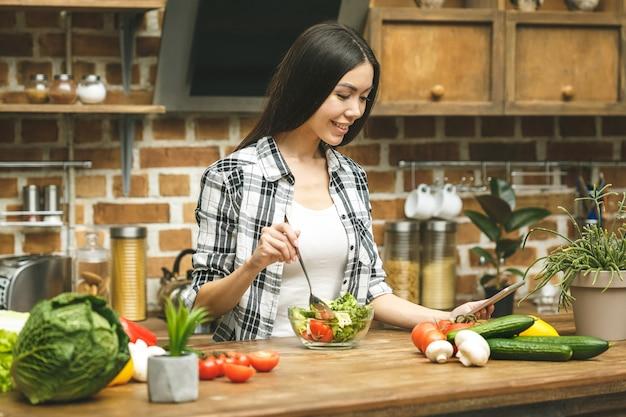 Jovem mulher bonita com computador tablet na cozinha, encontrar receitas e degustação de alimentos.