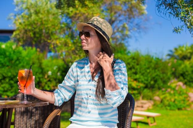 Jovem mulher bonita com coquetel no café oitdoor no resort exótico