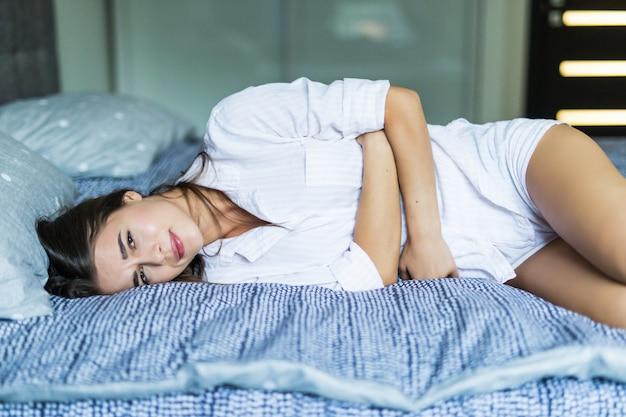 Jovem mulher bonita com dor, deitada na cama