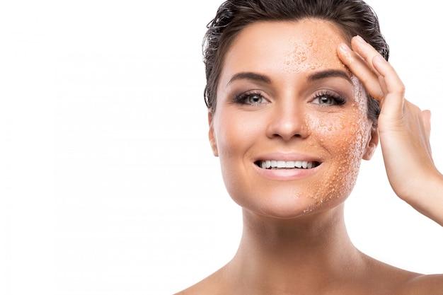 Jovem mulher bonita com esfoliante de açúcar no rosto
