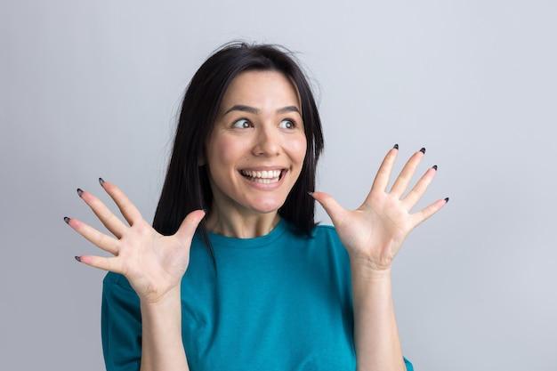 Jovem mulher bonita com expressão facial de surpresa em pé sobre um fundo cinza.