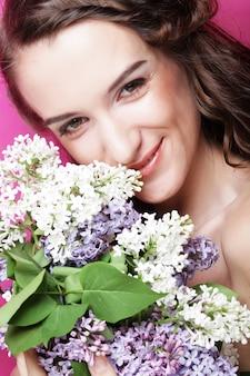 Jovem mulher bonita com flores lilás