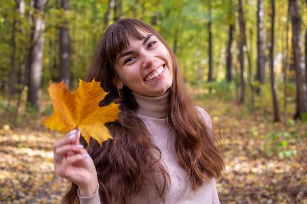 Jovem mulher bonita com folhas de outono sorrindo para a câmera no parque outono no sol brilha.
