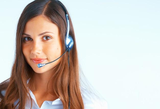 Jovem mulher bonita com fone de ouvido em fundo azul claro