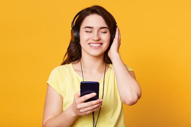 Jovem mulher bonita com fones de ouvido, ouvindo música favorita isolada em amarelo