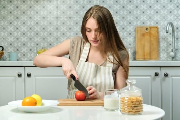 Jovem mulher bonita com frutas na cozinha, mulher sentada à mesa e cortando maçãs