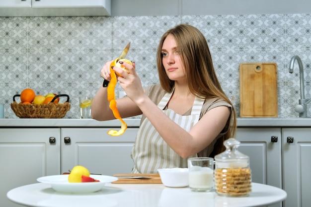 Jovem mulher bonita com frutas na cozinha, mulher sentada à mesa e limpeza de laranja. blogueira de culinária feminina cozinhando salada de frutas para a câmera