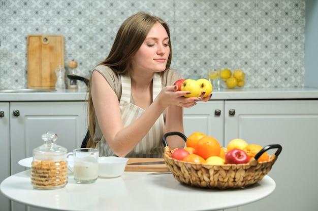 Jovem mulher bonita com frutas na cozinha, mulher sentada à mesa e segurando maçãs nas mãos