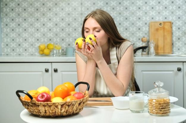 Jovem mulher bonita com frutas na cozinha, mulher sentada à mesa segurando maçãs