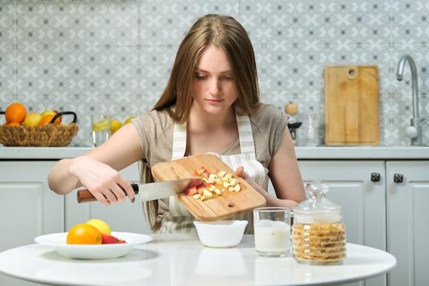 Jovem mulher bonita com frutas na cozinha