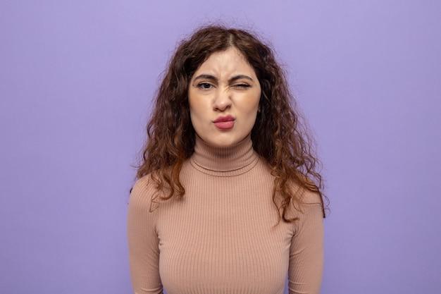 Jovem mulher bonita com gola alta bege e sorriso cético no rosto em pé sobre uma parede roxa