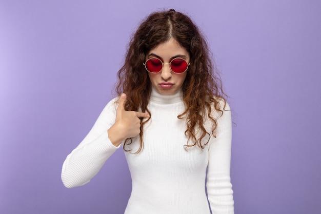 Jovem mulher bonita com gola alta e óculos vermelhos olhando para baixo com uma expressão triste apontando para si mesma com o dedo indicador