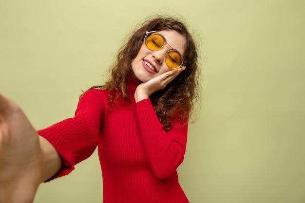 Jovem mulher bonita com gola alta vermelha usando óculos amarelos, feliz e alegre, sorrindo em pé sobre a parede verde