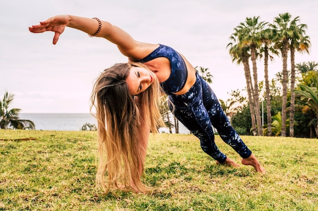 Jovem mulher bonita com longos cabelos loiros fazendo posição equilibrada de pilates no prado verde natural no esporte ao ar livre