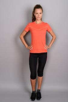 Jovem mulher bonita com longos cabelos loiros prontos para ginásio contra fundo cinza