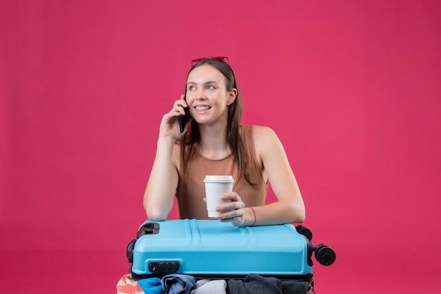 Jovem mulher bonita com mala de viagem, segurando a xícara de café, falando no celular, sorrindo sobre parede rosa