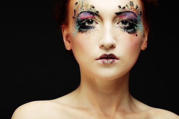 Jovem mulher bonita com maquiagem brilhante colorida