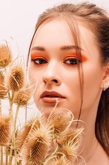 Jovem mulher bonita com maquiagem criativa e flores secas