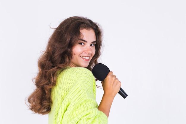 Jovem mulher bonita com maquiagem leve sardas em suéter na parede branca com microfone cantando feliz em movimento