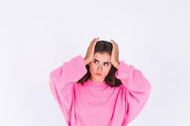 Jovem mulher bonita com maquiagem leve sardas em suéter na parede branca, sofrendo de dor de cabeça