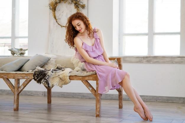 Jovem mulher bonita com o cabelo vermelho que senta-se no estúdio.