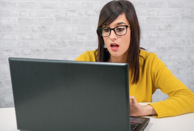 Jovem mulher bonita com o laptop no escritório