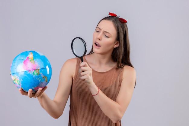 Jovem mulher bonita com óculos de sol na cabeça, segurando e olhando através de uma lupa no globo com interesse, sorrindo em pé sobre um fundo branco