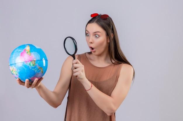 Jovem mulher bonita com óculos de sol na cabeça, segurando e olhando através de uma lupa no globo, surpresa e espantada em pé sobre um fundo branco