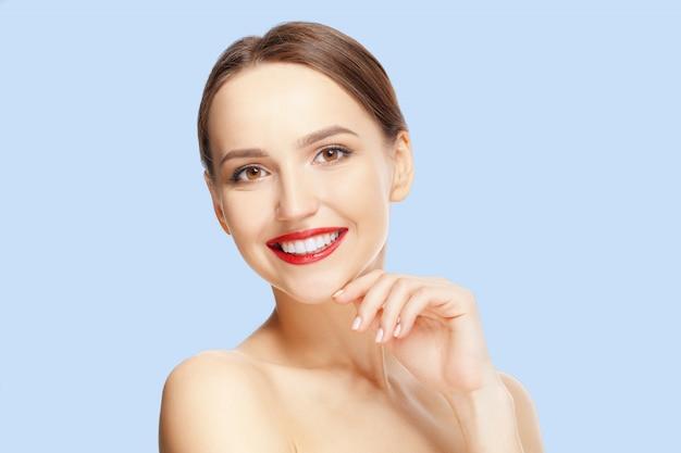 Jovem mulher bonita com os bordos frescos da pele e do vermelho que olham em linha reta e que demonstram os dentes saudáveis.