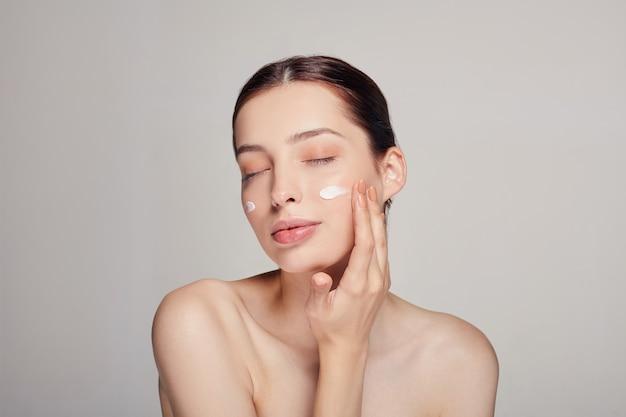 Jovem mulher bonita com os olhos fechados é aplicar creme cosmético no rosto. creme nas bochechas. cuidados com a pele. pele seca. conceito de beleza.