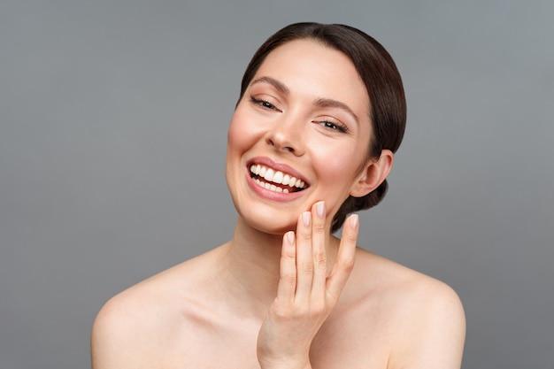 Jovem mulher bonita com pele perfeita tocando seu rosto e sorrindo cosmetologia beleza e spa