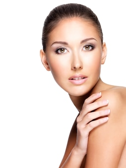 Jovem mulher bonita com pele saudável tocando seu ombro, isolado no branco.